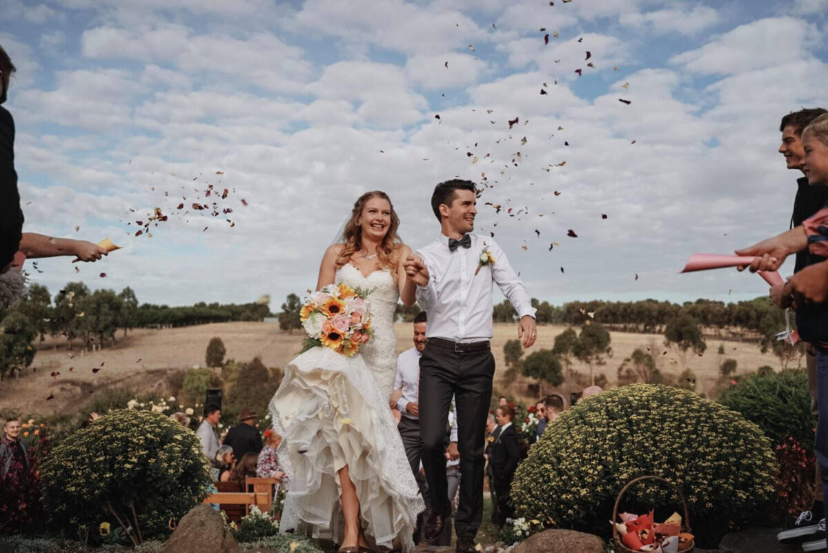 Shandar & Nathan happy on their wedding day with the sunflower bouquet